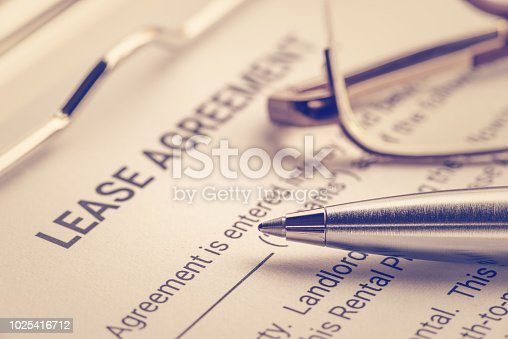 istock Business legal document concept : Pen and glasses on a lease agreement form. Lease agreement is a contract between a lessor and a lessee that allow lessee rights to use of a property owned by lessor 1025416712