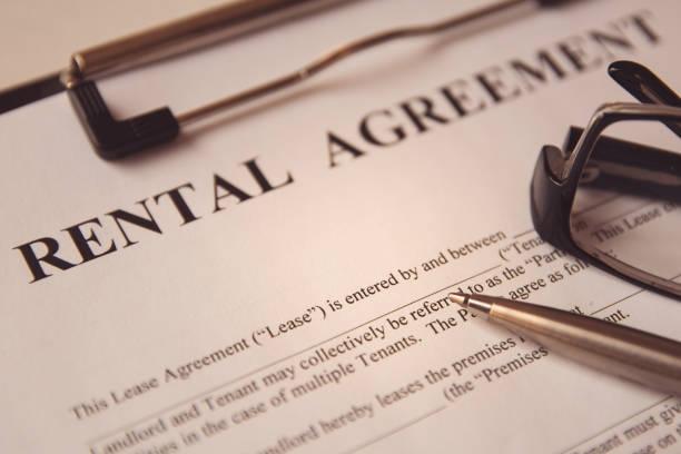 business legal document concept : pen and glasses on a rental agreement form. - locatario foto e immagini stock