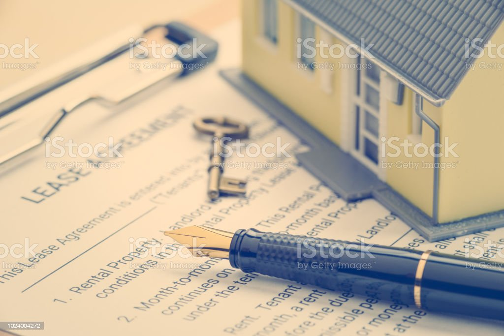 Pen, key, a house on a lease agreement form. Lease agreement is a...