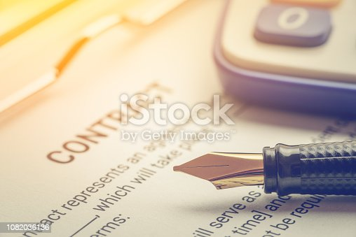 Business legal document, contract / agreement concept : Fountain pen on a business contract, a form on a clipboard. Contract is a voluntary, deliberate and legally binding agreement between parties.