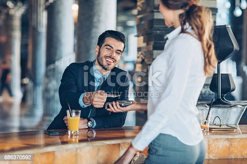Smiling businessman making contactless credit card payment in hotel's bar