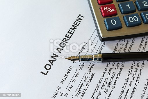 Business loan agreement or legal document concept. Fountain pen and calculator on loan agreement paper form. Loan agreement is a contract between a borrower and a lender.