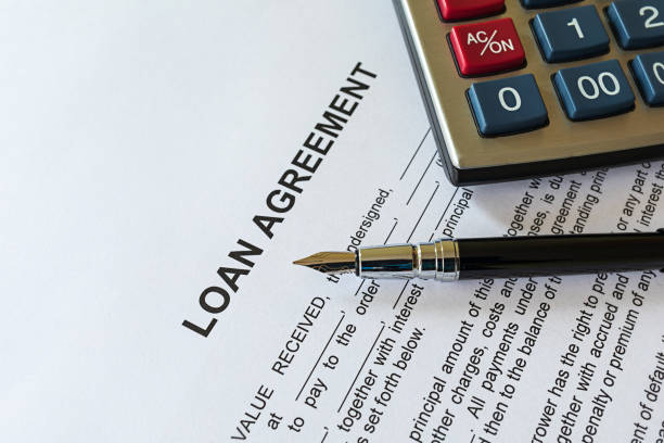 Business loan agreement or legal document concept. Fountain pen and calculator on loan agreement paper form. Business loan agreement or legal document concept. Fountain pen and calculator on loan agreement paper form. Loan agreement is a contract between a borrower and a lender. borrowing stock pictures, royalty-free photos & images