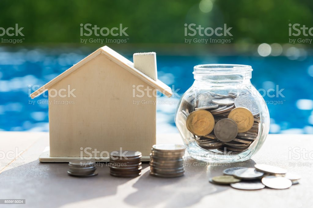 Business loans for real estate concept, a money bags put in a model home on the table on bokeh background in the public park. stock photo