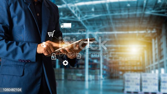 istock Business Logistics concept, Businessman manager touching icon for logistics on  Modern Trade warehouse background. Industry 4.0 concept 1050482104