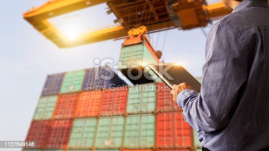 istock Business Logistics concept, Businessman manager using tablet check and control of Container Cargo ship with working crane bridge. Industry 4.0 concept 1127549148