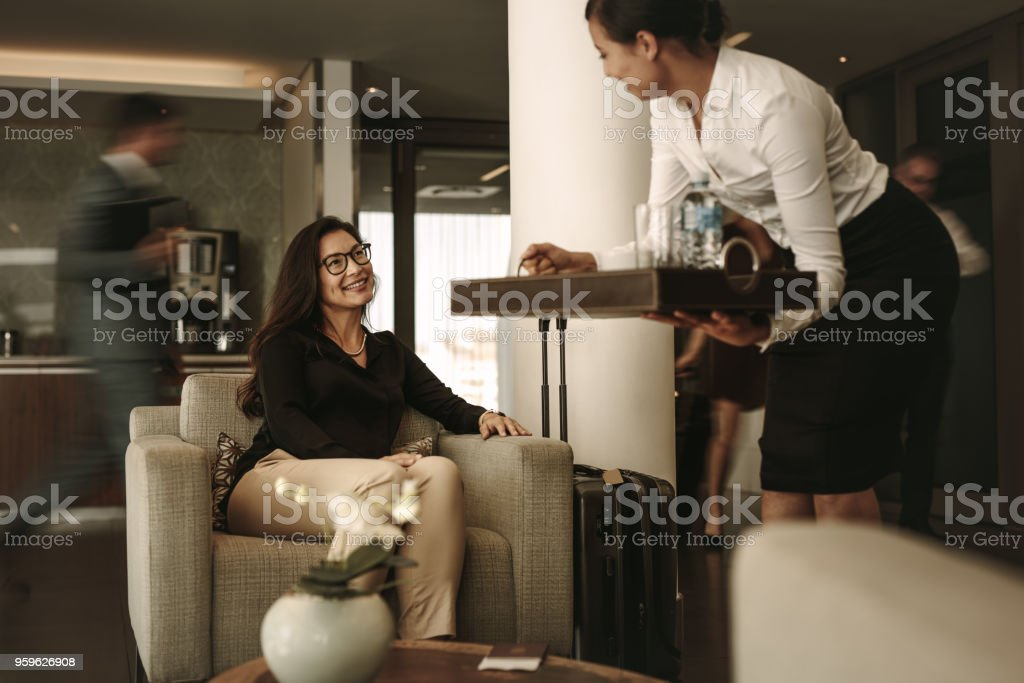 Business lounge staff serving coffee to female traveler stock photo