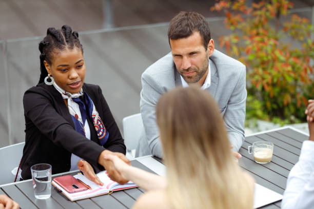 Business lunch A diverse group of businesspeople is having a meeting in an outdoor restaurant. Two women are shaking hands over the table. georgijevic coworking stock pictures, royalty-free photos & images
