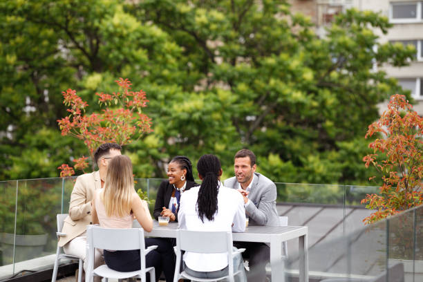 Business lunch A diverse group of businesspeople is having a meeting in an outdoor restaurant. georgijevic coworking stock pictures, royalty-free photos & images