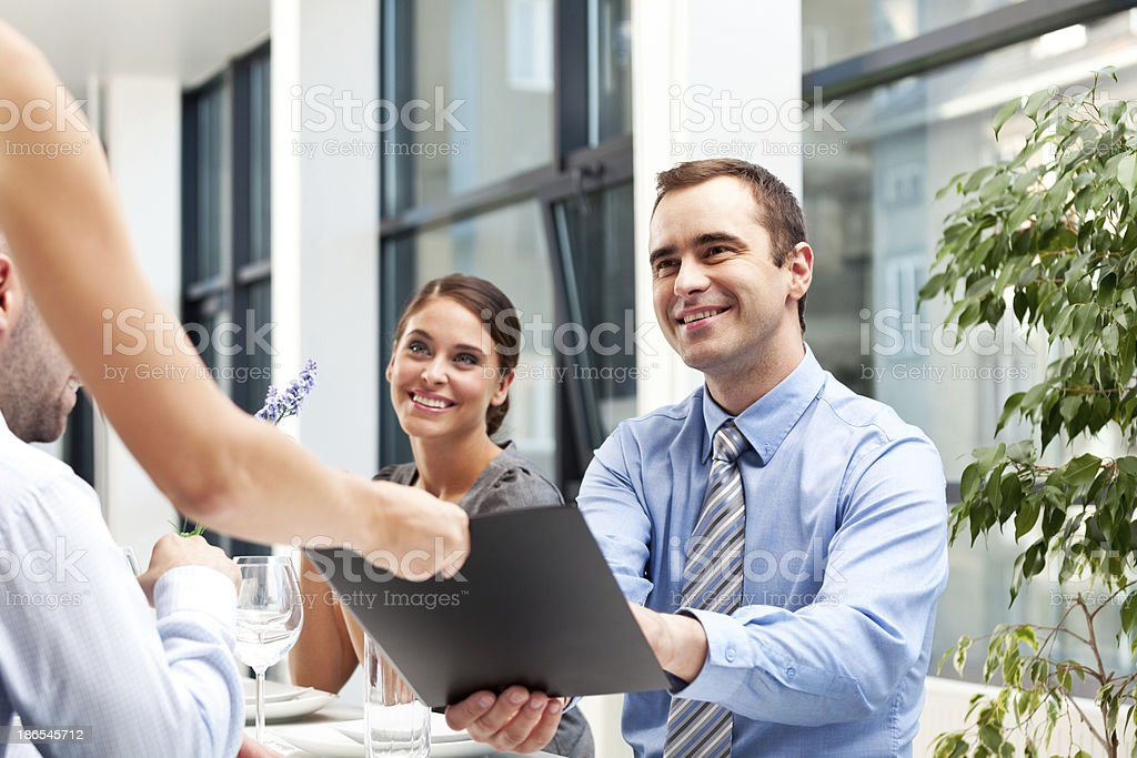 Business lunch Cheerful business people having a lunch break. Businessman receiving a menu from a waiter. Adult Stock Photo