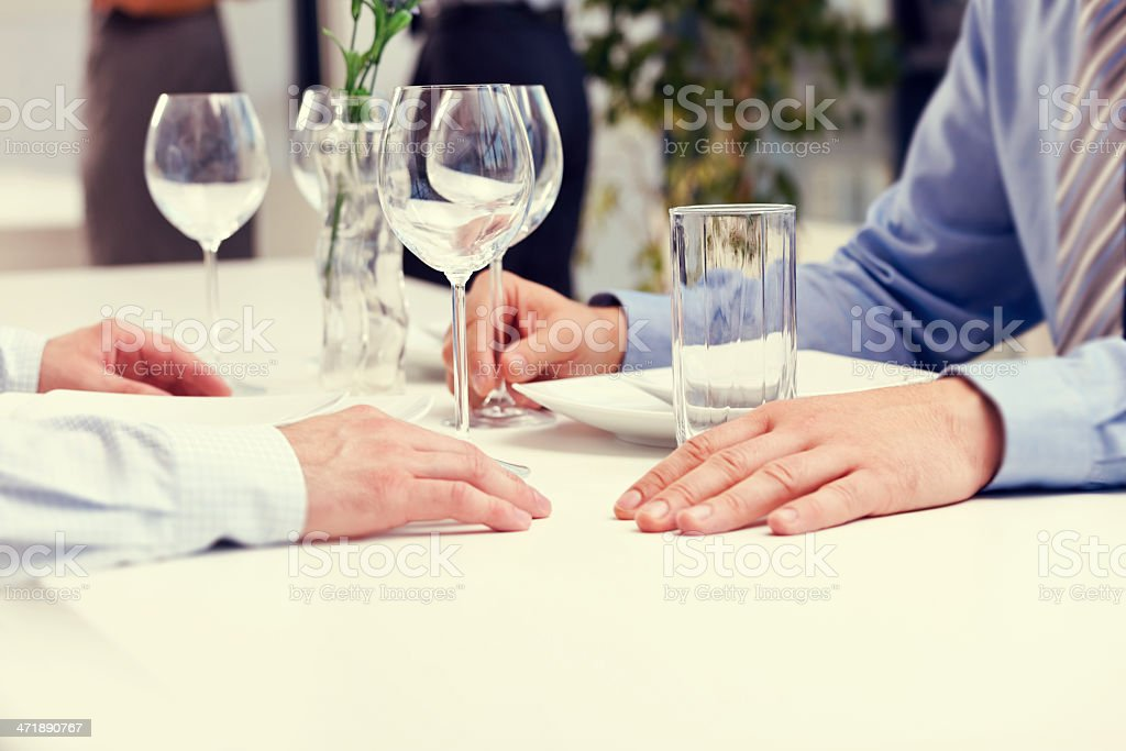 Business lunch Two businessmen having lunch in the restaurant. Close up of hands. Adult Stock Photo