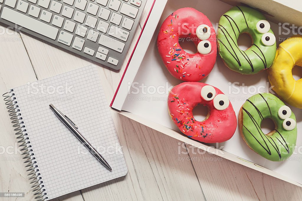 Business lunch snack in office, glazed donuts box top view stock photo