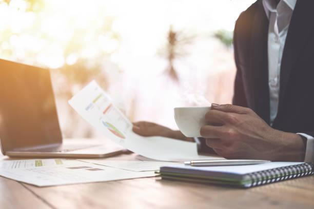テーブルの上のコーヒー、ラップトップ コンピューターのカップを持っているブリーフケース手集中型ビジネス男会計士探しドキュメントの作業 - パラリーガル ストックフォトと画像