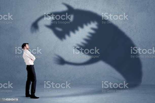 Business man afraid of his own shadow monster concept picture id1145845419?b=1&k=6&m=1145845419&s=612x612&h=gfvx6bu6q8lckvjpb4jyksf95dpg7fnsao6z7afrlgu=