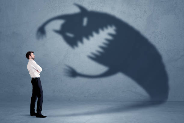 business man afraid of his own shadow monster concept - monster stock pictures, royalty-free photos & images