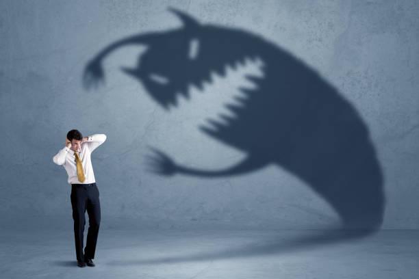 자신의 그림자 괴물 개념을 두려워하는 사업가 - 악한 뉴스 사진 이미지