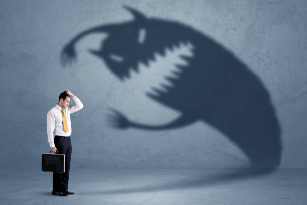Business man afraid of his own shadow monster concept stock photo