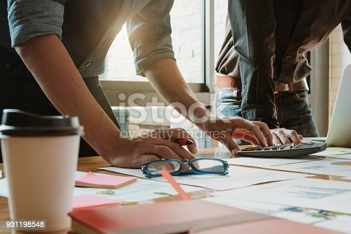 istock Business man analysis on data paper with partner during using calculator for calculating financial at the office - Business team meeting concept 931198548