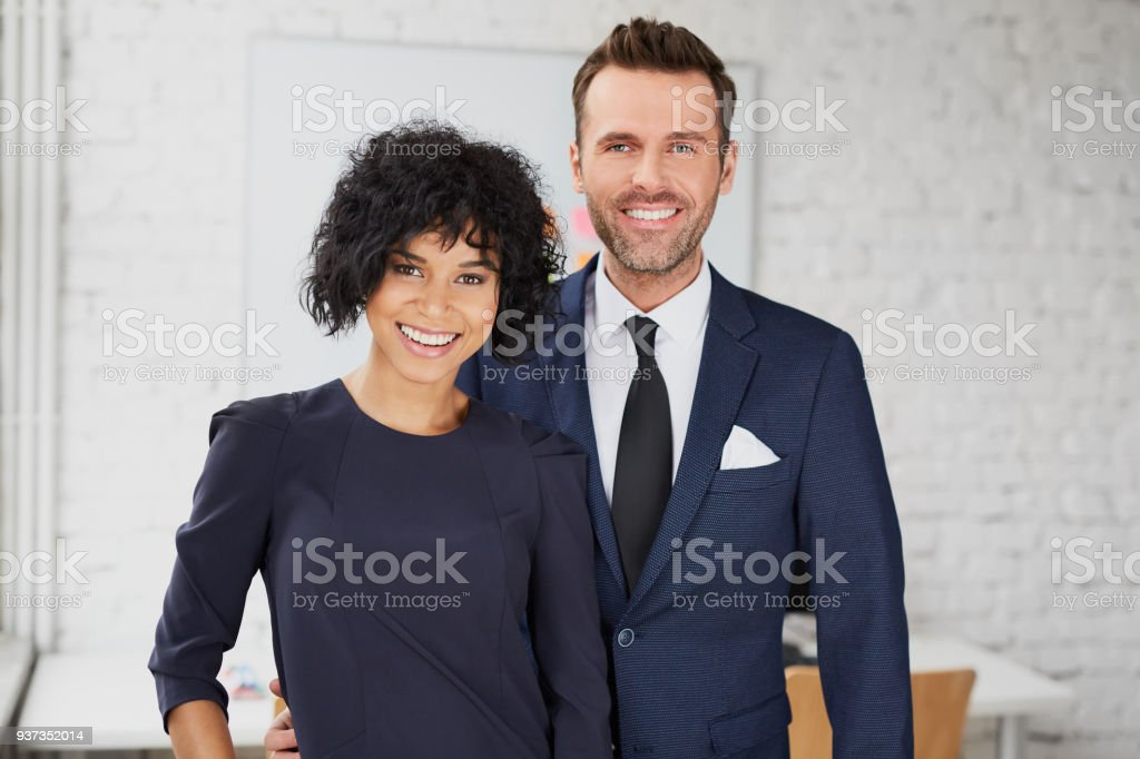 Business man and business woman standing together in the office stock photo