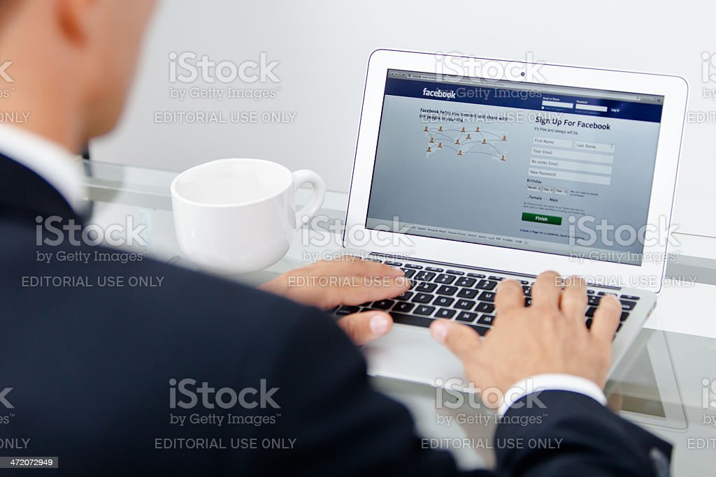 Business man and Facebook at work stock photo