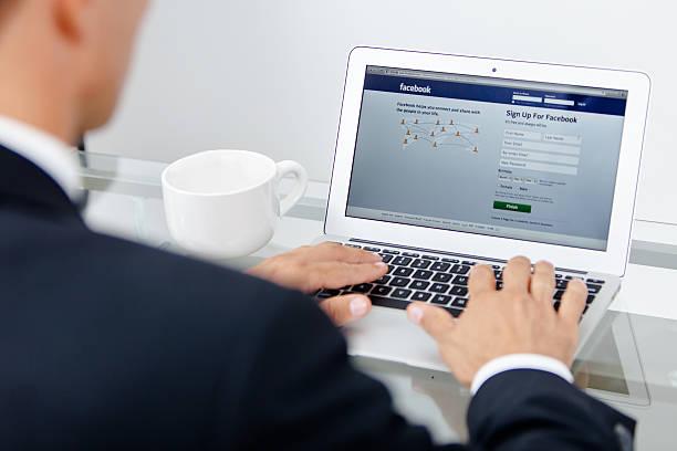 business-mann und facebook bei der arbeit - www kaffee oder tee stock-fotos und bilder