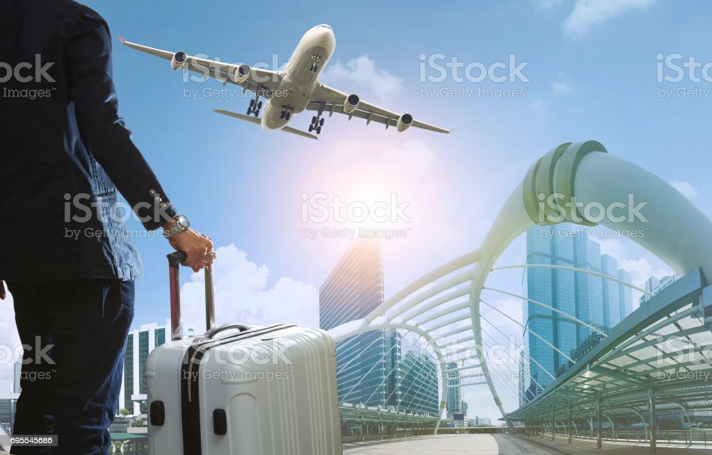 business man and traveling luggage in city life with plane flying over skyscraper stock photo