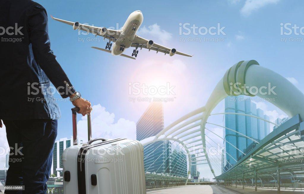 hombre de negocios y viaje equipaje en vida de la ciudad con el avión volando sobre los rascacielos - foto de stock