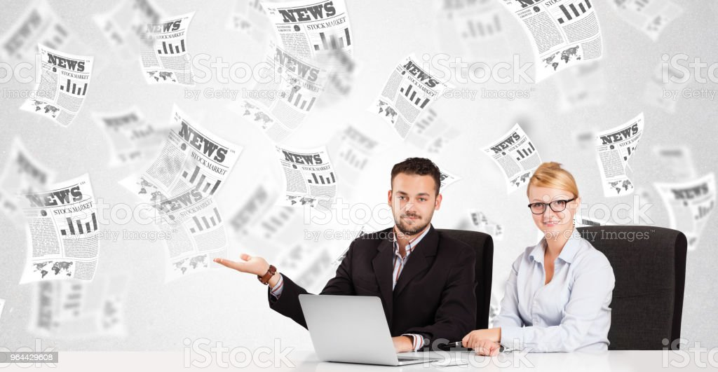 Business man and woman at desk with stock market newspapers - Royalty-free Article Stock Photo