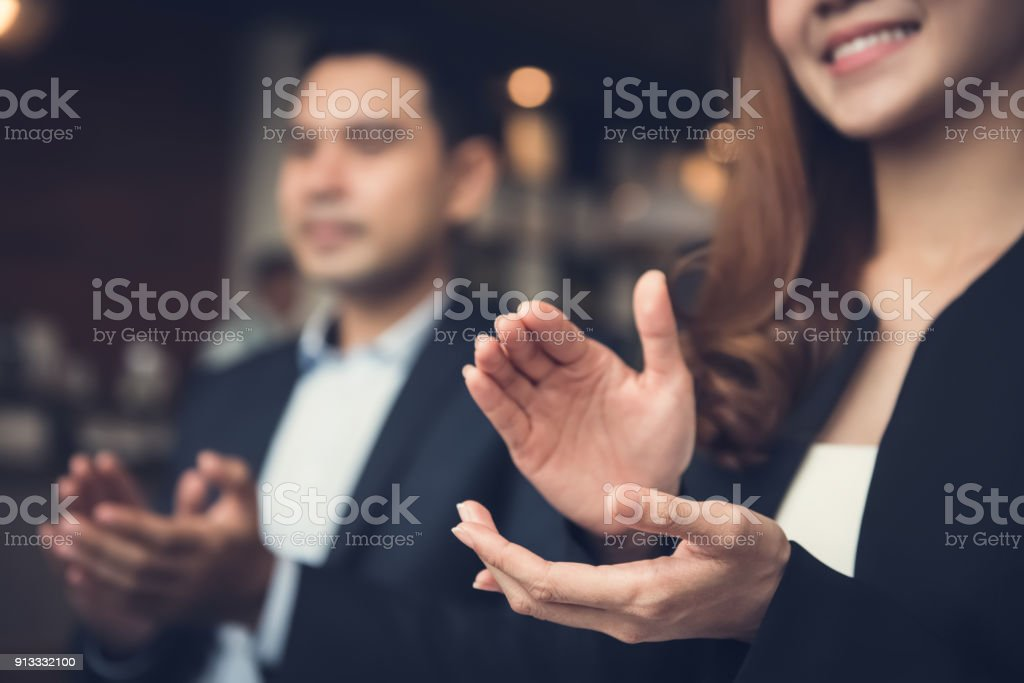 Business man and woman clapping hands at business meeting stock photo