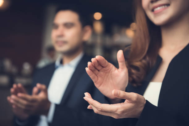 business man and woman clapping hands at business meeting - applaudire foto e immagini stock