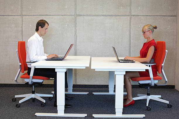 business man and woman in correct sitting posture at workstations stock photo