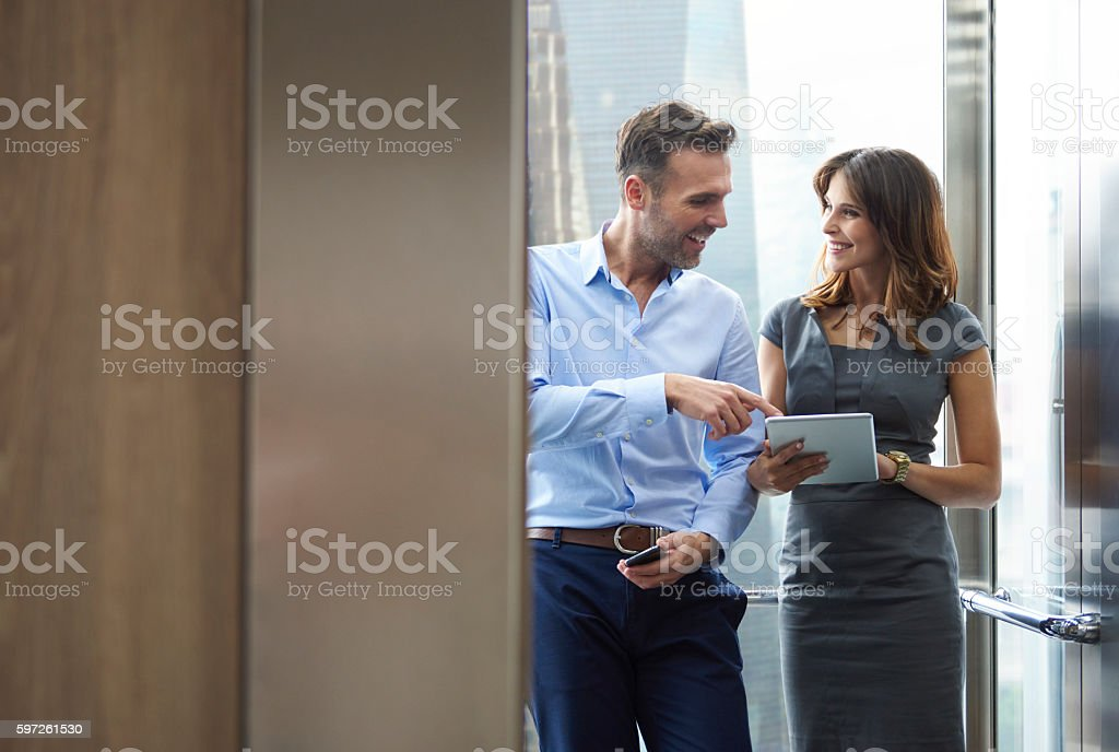 Business man and woman in the elevator stock photo