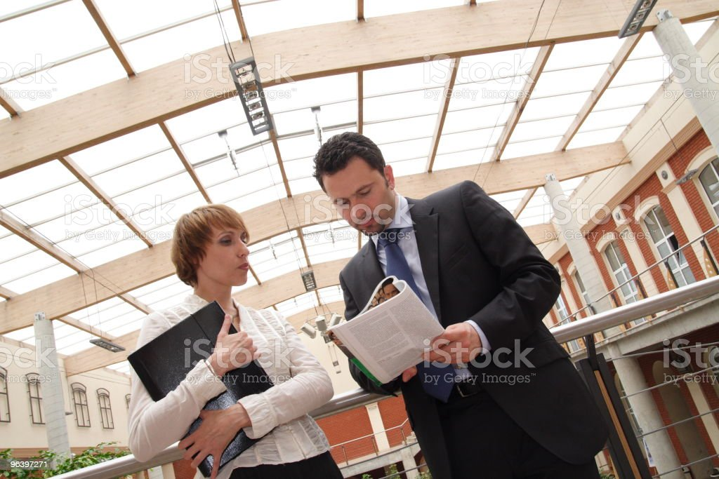business man and woman reading news in magazine - Royalty-free Administrator Stock Photo