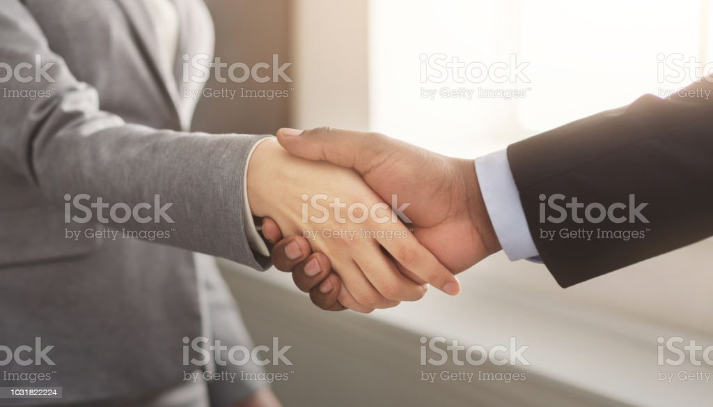 Business man and woman shaking hands stock photo