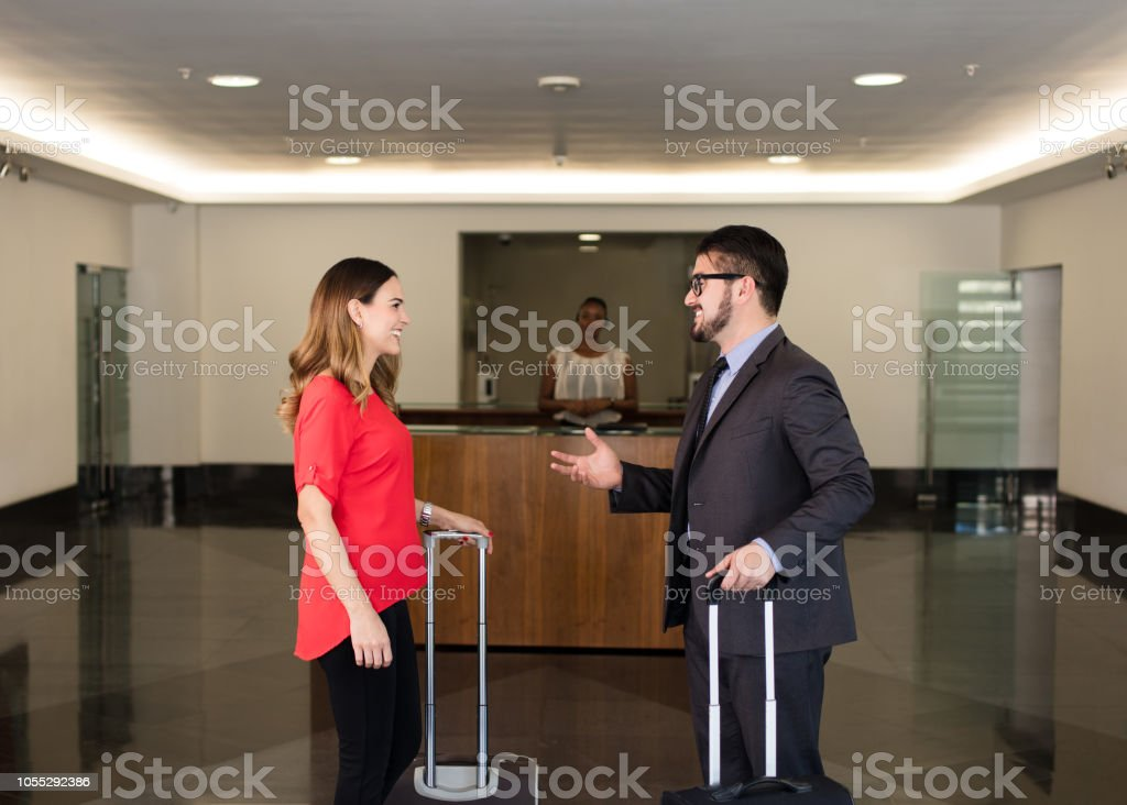 Business man and woman talking in lobby stock photo