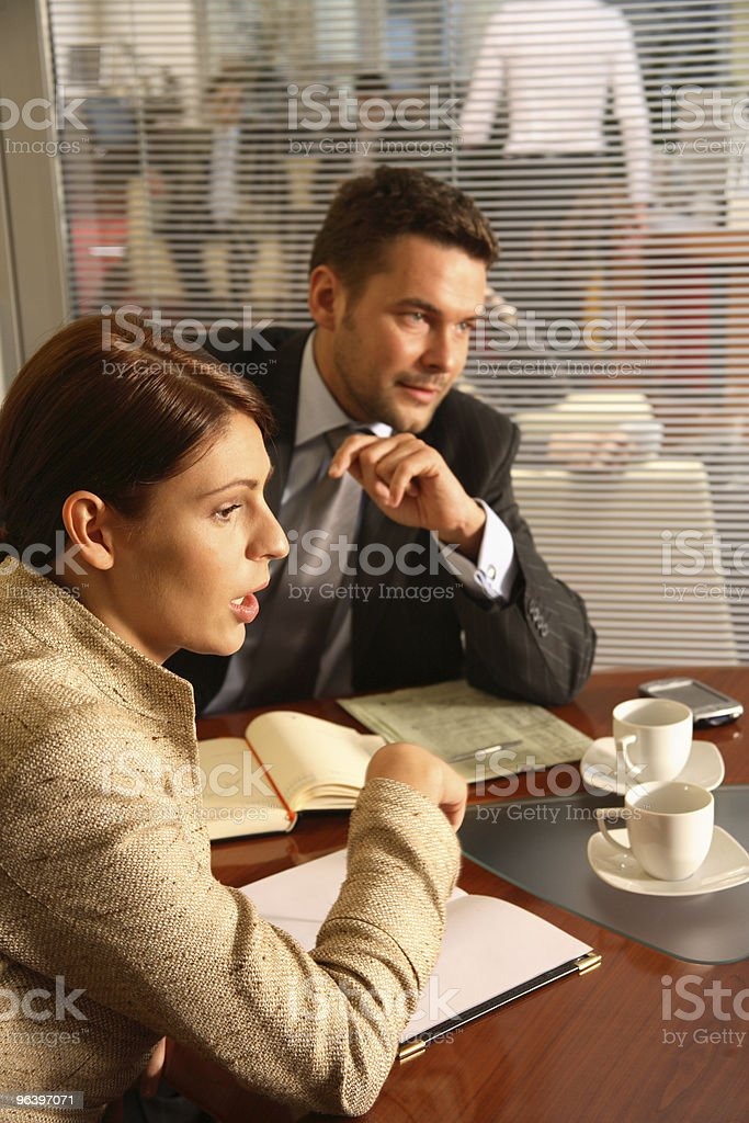 Business man and woman talking in the office environment stock photo