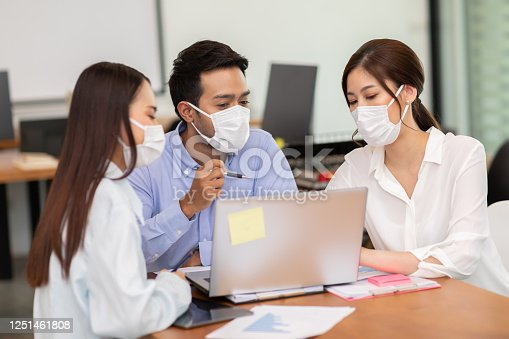 Business man and woman wearing face mask meeting and working together for discussion and brainstroming to get ideas or marketing solution with social distance due virus pandemic