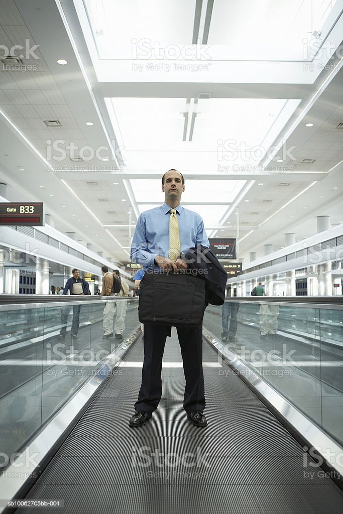 Business man at airport, carrying briefcase and jacket royalty-free stock photo