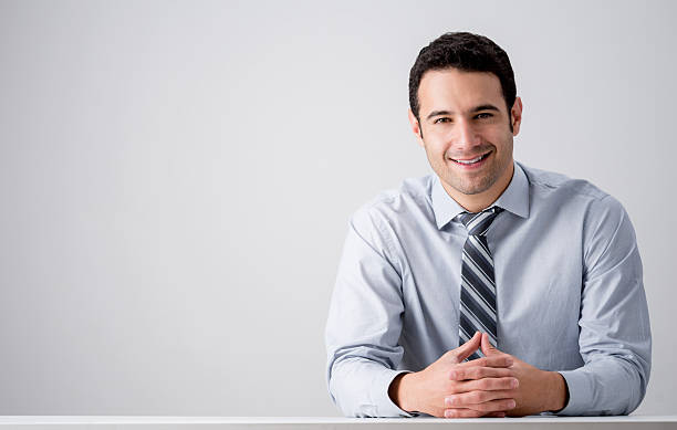 Business man at his desk Successful business man sitting at his desk salesman stock pictures, royalty-free photos & images