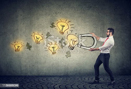istock Business man attracts bright ideas light bulbs with a magnet 1136688099