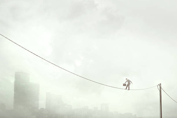 business man balancing on a electric wire over the city - alambre fotografías e imágenes de stock