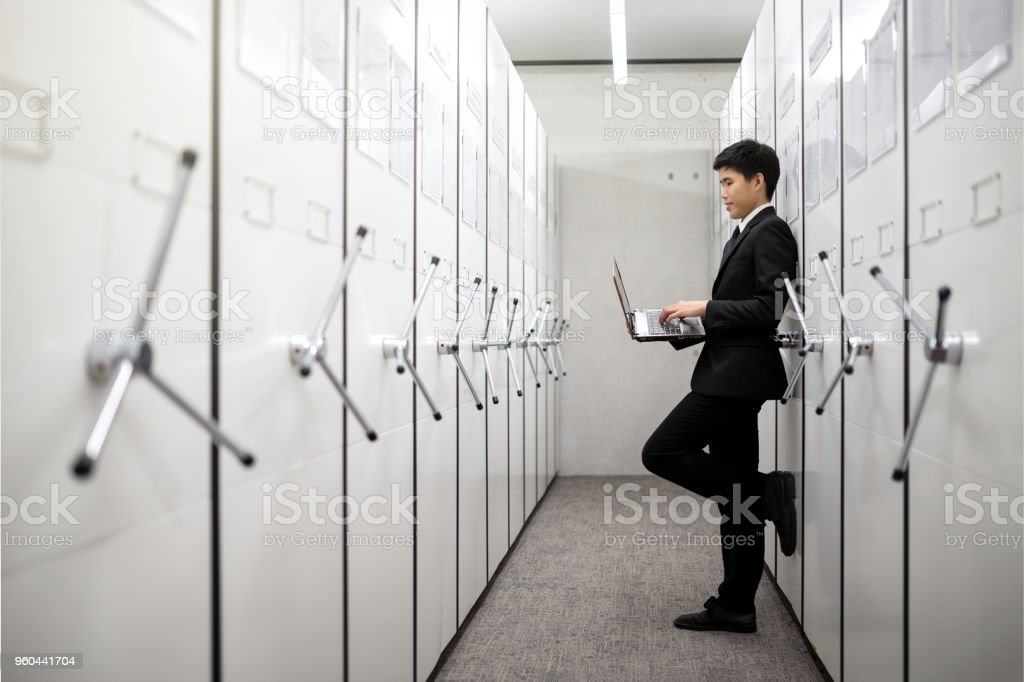 Business man, bank manager using notebook in a locker server room, safe deposit boxes with vault door. стоковое фото