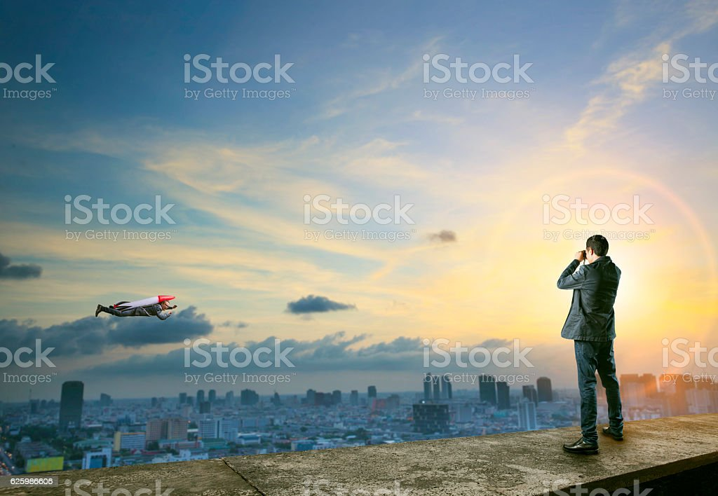 business man binocular to man with rocket on back flying stock photo