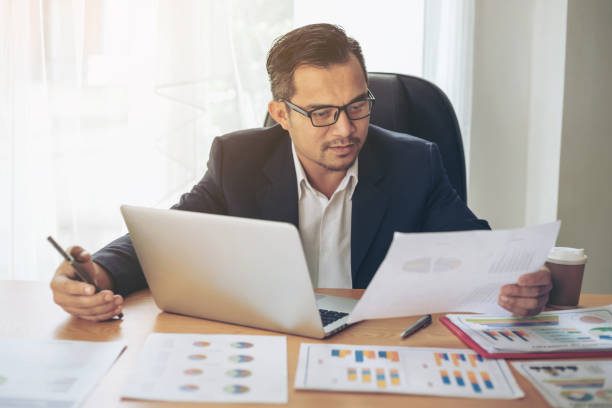 Business man busy standing at office desk  on documents  working  , business concept stock photo