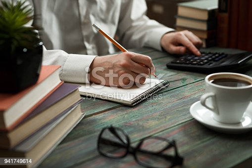 645670208istockphoto Business man calculate about cost and doing finance at office 941749614