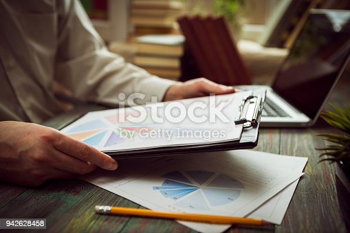 645670208istockphoto Business man calculate about cost and doing finance at office 942628458