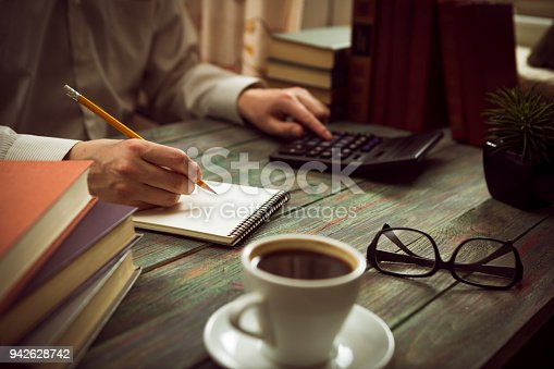 645670208istockphoto Business man calculate about cost and doing finance at office 942628742