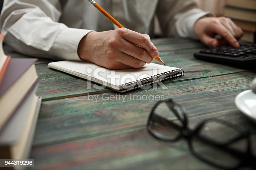 645670208istockphoto Business man calculate about cost and doing finance at office 944319296