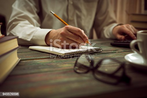 645670208istockphoto Business man calculate about cost and doing finance at office 945526598