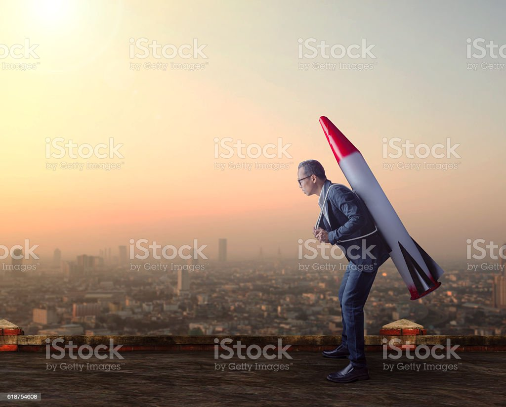 business man carries rocket missile on high building stock photo